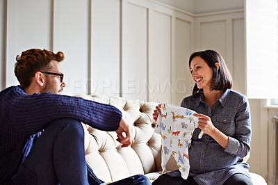 Buy stock photo Shot of a young pregnant woman showing her husband baby clothes on their sofa