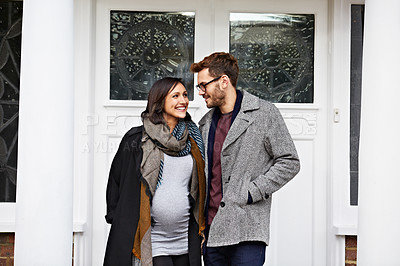 Buy stock photo Short of a pregnant woman and her husband standing on their front porch in autumn