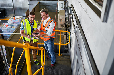 Buy stock photo Shot of two warehouse workers standing on stairs using a digital tablet