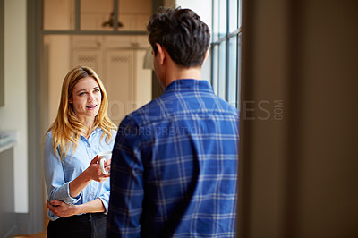 Buy stock photo Shot of a young couple drinking coffee together by their kitchen window