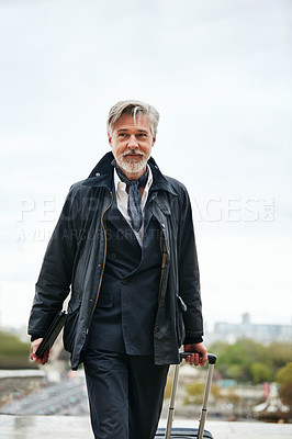 Buy stock photo Shot of a mature man pulling a suitcase while walking through the city