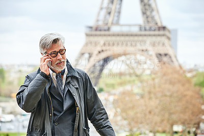 Buy stock photo Shot of a handsome mature man talking on a cellphone in Paris with the Eiffel Tower in the backgournd
