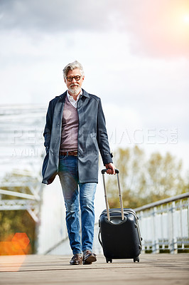 Buy stock photo Shot of a mature man pulling a suitcase while walking over a bridge in the city