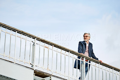 Buy stock photo Shot of a mature man admiring the view while leaning on the railing of a bridge