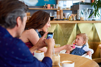 Buy stock photo Shot of a father taking a picture of his wife and baby girl while sitting in a cafe
