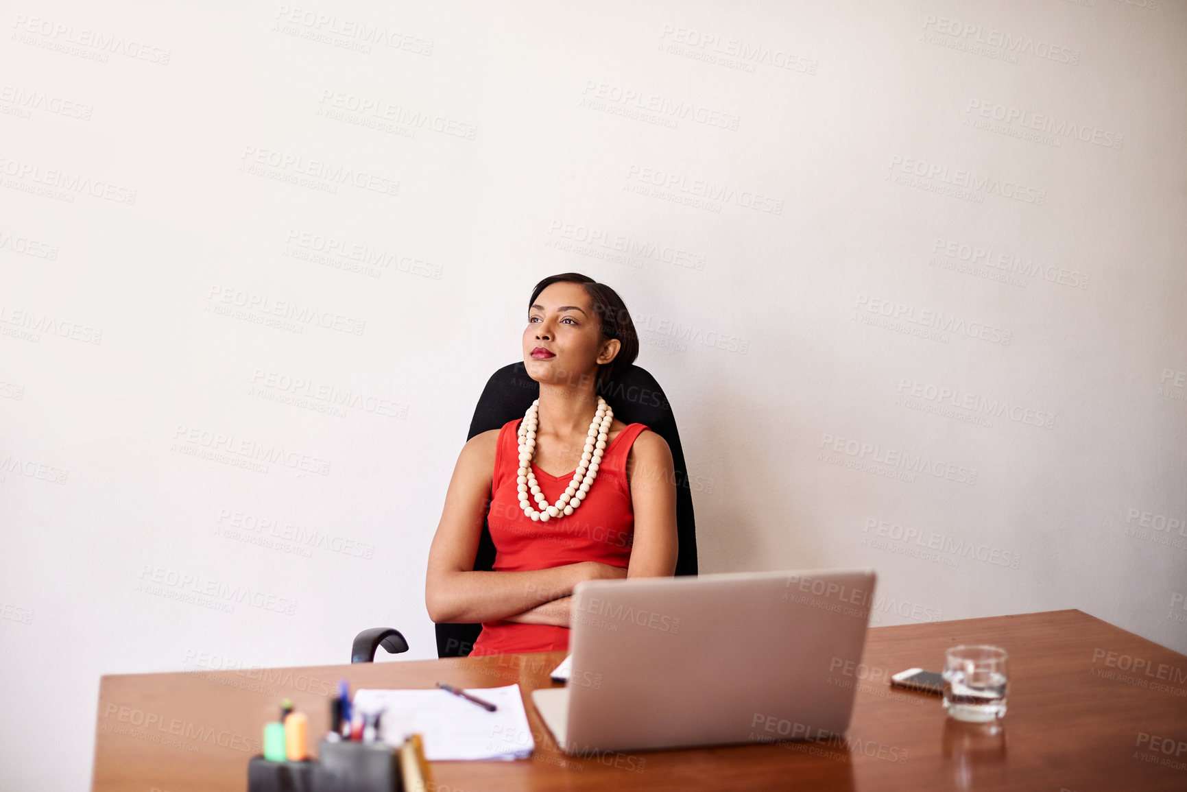 Buy stock photo Shot of a businesswoman sitting at her desk leaning back in her chair