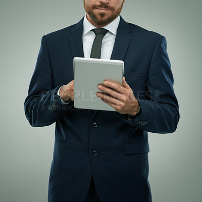 Buy stock photo Studio shot of a corporate businessman using his digital tablet against a grey background