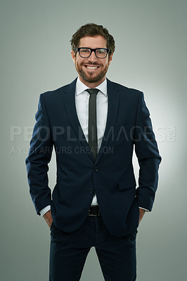 Buy stock photo Studio portrait of a corporate businessman standing with his hands in his pockets against a grey background