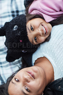 Buy stock photo Cropped portrait of a little girl and her mother lying on a blanket outside together