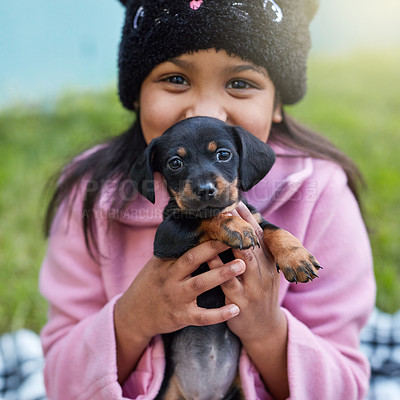 Buy stock photo Cropped portrait of a cute little girl cuddling her puppy while sitting outside