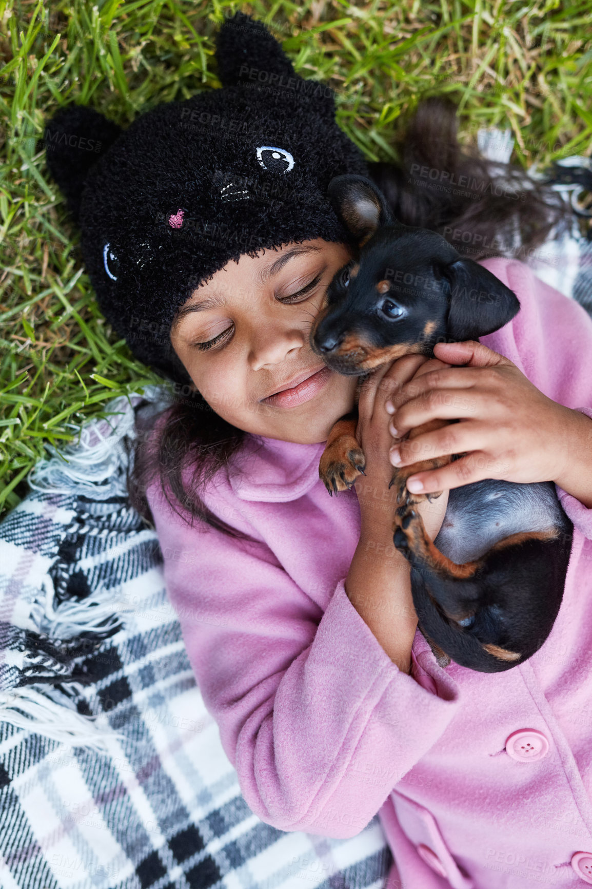 Buy stock photo Cropped shot of a cute little girl cuddling her puppy while lying on a blanket outside