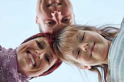 Buy stock photo Low angle portrait of a cute little girl and her parents putting their heads together