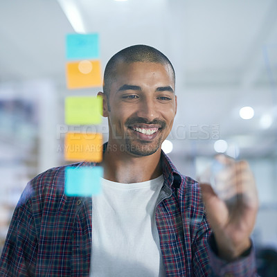 Buy stock photo Cropped shot of a young designer working on a glass wall in the office