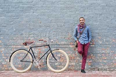 Buy stock photo Portrait of a young man posing with his bicycle against a grey wall in the city