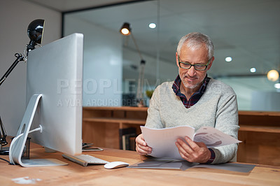 Buy stock photo Shot of a smiling mature businessman reading paperwork while sitting at his desk in an office
