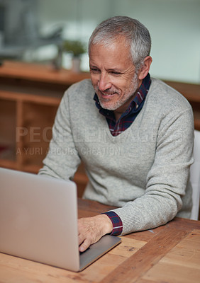 Buy stock photo Shot of a smiling mature businessman using a laptop while working in an office