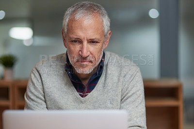 Buy stock photo Shot of a mature businessman using a laptop while working in an office