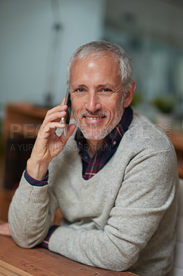 Buy stock photo Portrait of a mature businessman talking on a cellphone while working in an office