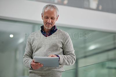 Buy stock photo Shot of a mature businessman using a digital tablet while standing in an office