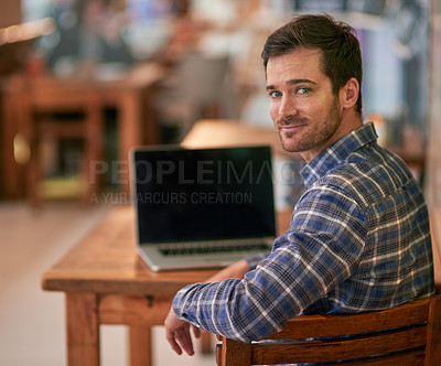 Buy stock photo Portrait of a young man using his laptop while sitting in a coffee shop