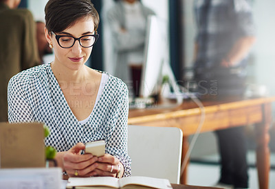 Buy stock photo Cropped shot of a young businesswoman texting on a cellphone in an office