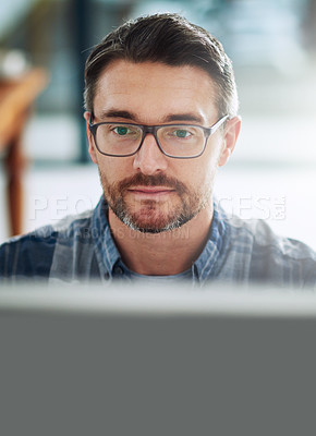 Buy stock photo Portrait of a mature businessman working on a computer in an office