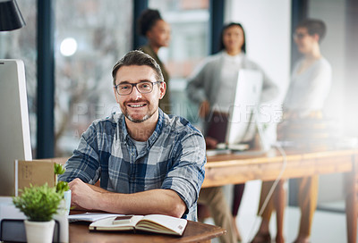 Buy stock photo Portrait of a mature businessman sitting at his desk with colleagues in the background