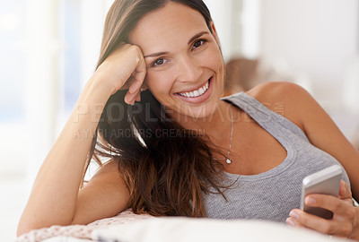 Buy stock photo Cropped shot of a woman using her phone while relaxing at home