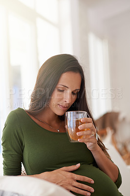Buy stock photo Shot of a pregnant woman relaxing at home with a glass of tea