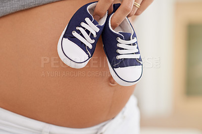 Buy stock photo Cropped shot of a woman holding baby shoes against her pregnant belly