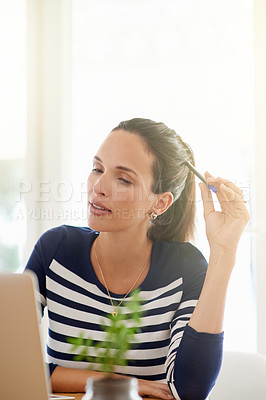 Buy stock photo Cropped shot of a young woman working on a laptop at home