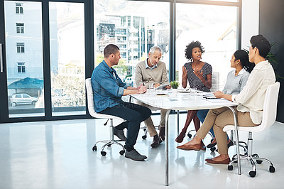 Buy stock photo Shot of a group of coworkers talking together while sitting at a table in a meeting in an office