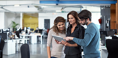 Buy stock photo Cropped shot of three colleagues looking at a tablet in the office