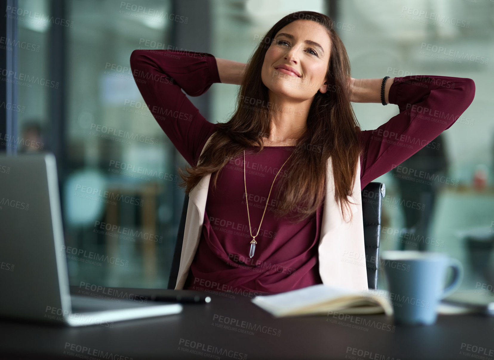 Buy stock photo Shot of a businesswoman looking relaxed while sitting behind her laptop