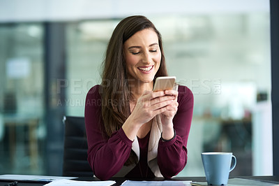 Buy stock photo Shot of a businesswoman using her cellphone at her desk