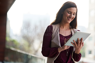 Buy stock photo Shot of a businesswoman using her tablet while standing outside