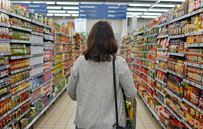 Buy stock photo Rear view shot of a woman browsing through an aisle in a grocery store