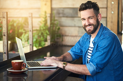 Buy stock photo Portrait of a handsome young man working on his laptop in a cafe