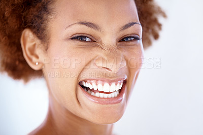 Buy stock photo Closeup portrait of a pretty young female laughing against grey background