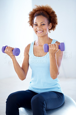 Buy stock photo Portrait of beautiful young woman working out with dumbbell sitting on fitness ball