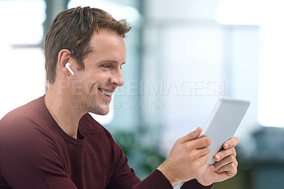 Buy stock photo Shot of a young man using wireless earphones and a digital tablet