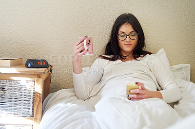 Buy stock photo Cropped shot of a young woman texting on her cellphone and drinking coffee while in bed