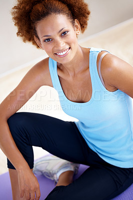Buy stock photo Portrait of a fit young woman performing yoga on a mat indoors