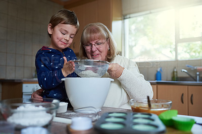 Buy stock photo Cropped shot of a woman baking with her grandson at home