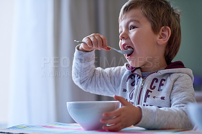 Buy stock photo Cropped shot of a little boy eating breakfast at home