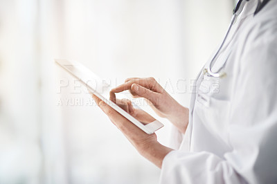 Buy stock photo Closeup shot of a female doctor using a digital tablet in a hospital corridor