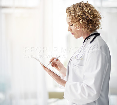 Buy stock photo Shot of a female doctor using a digital tablet in a hospital corridor