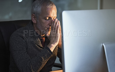 Buy stock photo Cropped shot of a mature businessman looking stressed while working late at the office