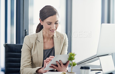 Buy stock photo Shot of a professional businesswoman using a digital tablet at her office desk