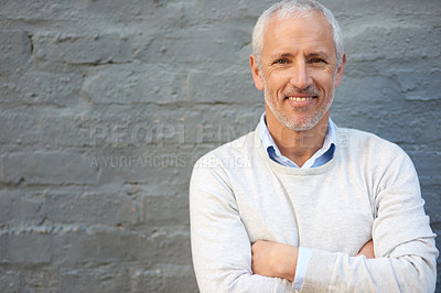 Buy stock photo Portrait of a mature businessman standing with his arms folded against a brick wall
